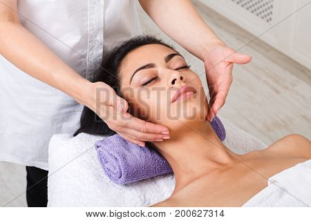 Neck massage in spa. Female beautician work in wellness center. Professional massagist make relax healthy procedure to beautiful indian girl in cosmetology cabinet or beauty parlor.