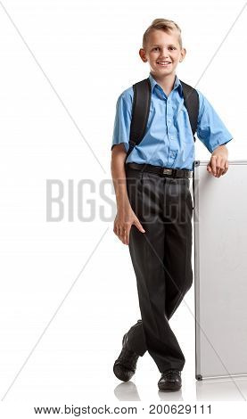 Modern male pupil with schoolbag standing near whiteboard