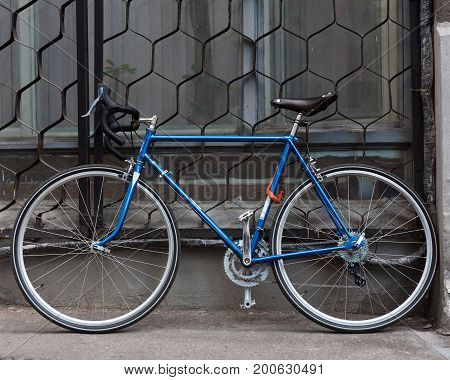 Bright blue Fixed Gear beautiful vintage bicycle stands on the street. Hipster. Outdoor.