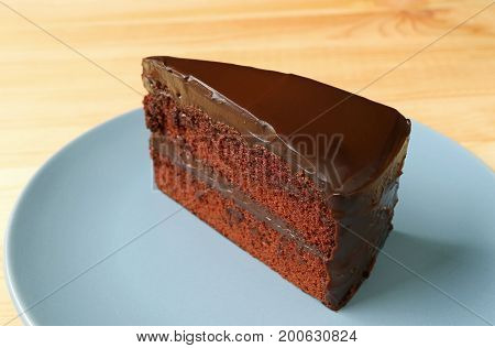 Piece of Delectable Chocolate Layer Cake Served on Blue Plate on the Wooden Table