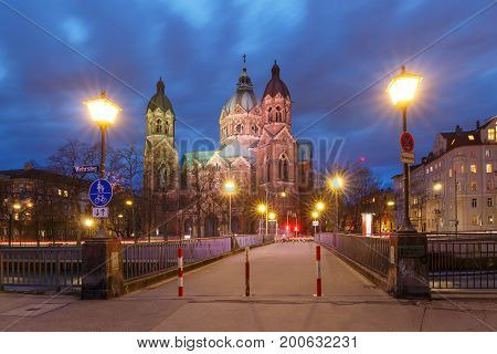 Saint Lucas Church, the largest Protestant church in Munich, and bridge across Isar River at night, Bavaria, Germany