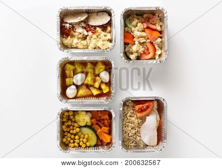 Healthy daily meals, food delivery. Take away of natural fitness dishes for diet. Lunch in foil boxes on white background