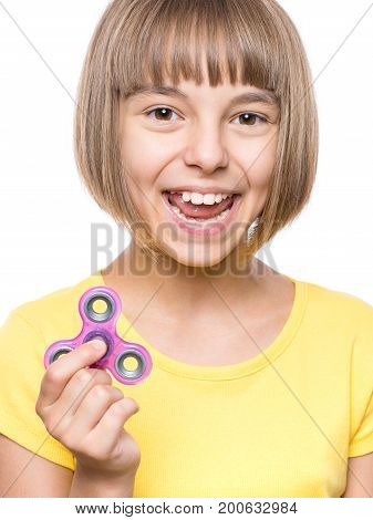 Young girl holding popular fidget spinner toy - close up portrait. Happy smiling child playing with Spinner, isolated on white background.