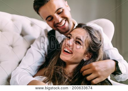 A Young Couple In Love Having Fun On A Sofa And Playing With A Hair Of The Girl. Cheerful Bride And