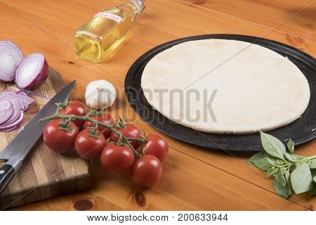 Pizza base surrounded with garlic, tomatoes, onions, olive oil and basil