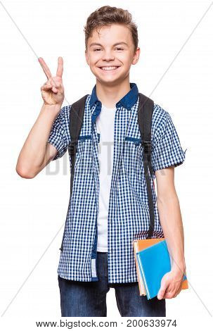Portrait of young student with school bag and books. Teenager smiling, making victory gesture and looking at camera. Happy teen boy, isolated on white background.