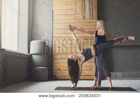 Yoga instructor and young woman in side plank at stretching class, vasisthasana exercise. Fit yoga girl balancing on mat indoors at fitness studio gym