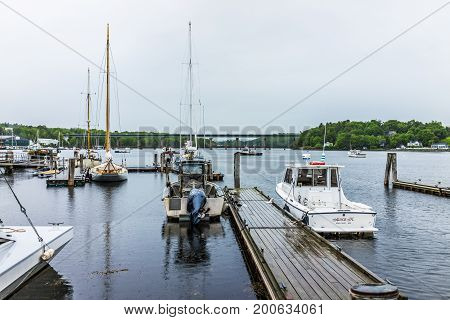 Belfast USA - June 9 2017: Empty marina harbor in small village in Maine during rain with boats and wooden dock
