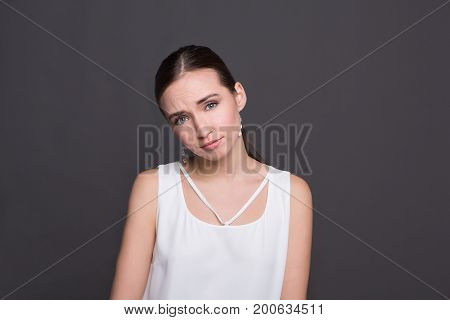 Confused attractive girl portrait. Shocked and surprised young woman looking at camera, dark background