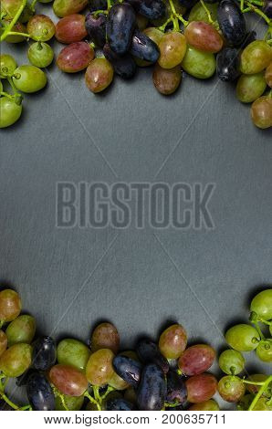 Grapes on dark background with copy space. Vertical frame.