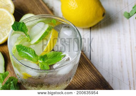 Cold lemonade with lemon mint and cucumber in glass.