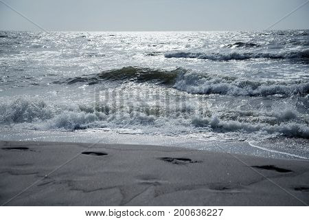sea coast with footprints and stormy sea under moonlight