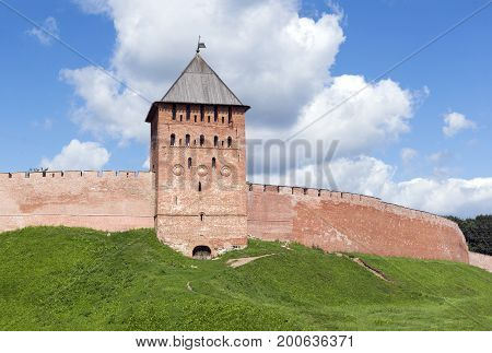 brick tower and wall of medieval fortress of the 11th century Novgorod Kremlin grass sky with clouds
