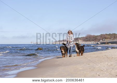 woman with bernese mountain dog on sea beach