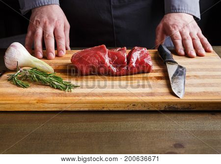 Male chef preparing filet mignon for cooking at restaurant kitchen. Fresh meat, garlic and rosemary for marinade on wooden board. Modern cuisine backgroung with copy space