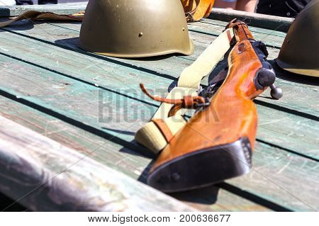 Old military helmet and rifle on a wooden background