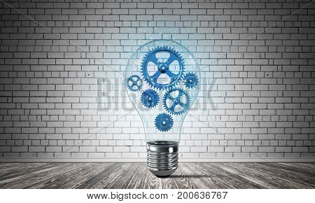 Glass lightbulb with multiple blue gears inside placed in empty room with grey brick wall on background. 3D rendering.
