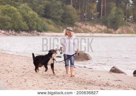 woman with her dog on sea beach walking