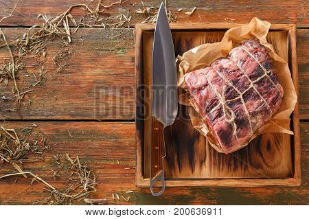 Raw black angus beef bound with rope in craft paper on cutting board. Aged prime marble meat and sharp chef knife at rustic wood background, top view, copy space