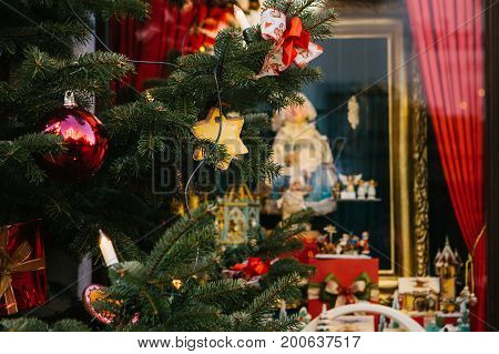 Christmas fir-tree decorated with toys on the foreground. Selective focus. Christmas background decorations.