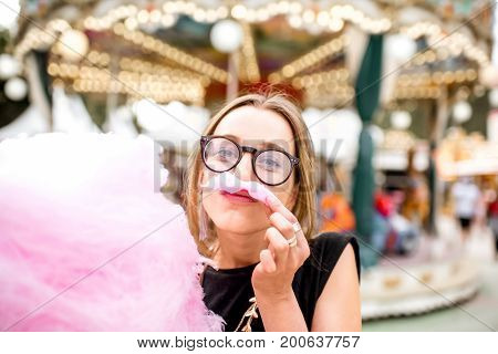 Young woman making mustache with pink cotton candy standing outdoors at the amusement park