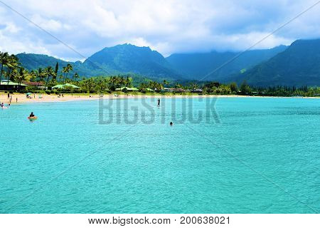 August 1, 2017 at Hanalei Bay in Kauai, HI:  People swimming in turquoise waters and sunbathing at Hanalei Bay Beach with mountains beyond where people can relax at a tropical beach while viewing the beautiful surrounding landscape taken in Kauai, HI