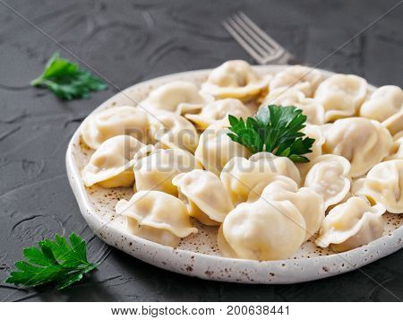 Traditional russian pelmeni, ravioli, dumplings with meat on black concrete background. Russian food and russian kitchen concept.