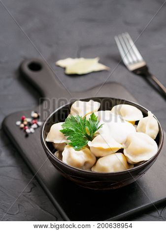 Traditional russian pelmeni, ravioli, dumplings with meat on black cutting board over black concrete background. Russian food and russian kitchen concept.