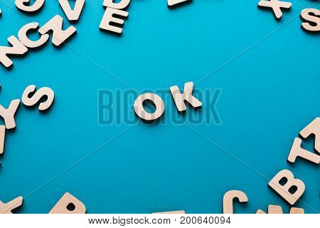 Word OK on blue background, in wooden letters frame. Positivity, success, wellbeing concept