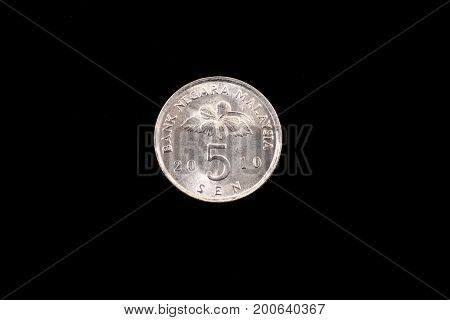 An extreme close up of an Malaysian five sen coin on a solid black background