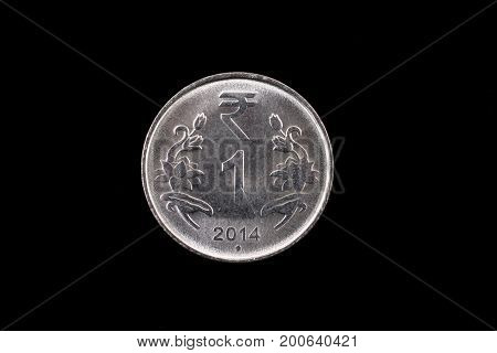 An extreme close up of an Indian one rupee coin on a solid black background