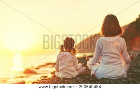 Happy family mother and child daughter doing yoga meditate in lotus position on beach at sunset