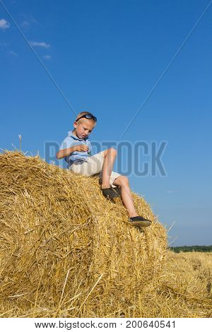 boy held in the hands of a green horse sitting on the hay in the field