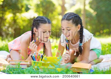 Happy Hispanic Girls Drawing And Studying In Park