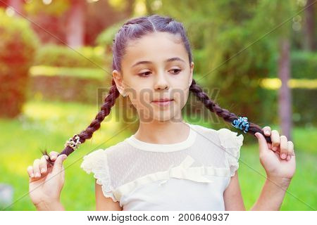 Portrait Of Pretty Young Girl With Pigtails At Sunny Day