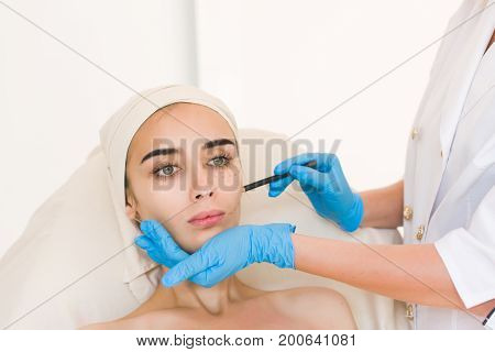 Plastic surgery concept. Hand in blue glove marking women face against white background.
