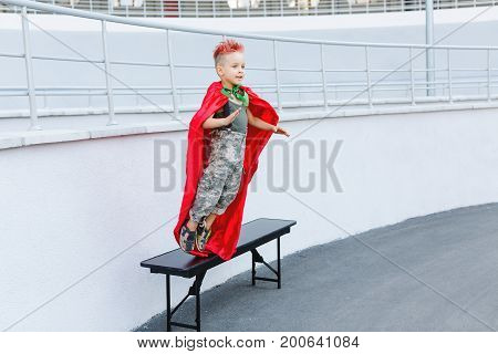 Happy little child playing superhero. Kid having fun outdoors. Kid superhero in a red cloak.A little boy with red hair. Child in uniform. The boy jumps from the bench