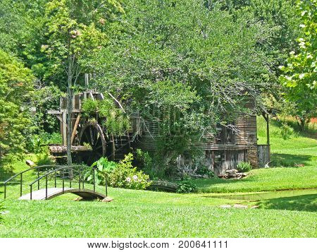 a small bridge leads to an old gristmill