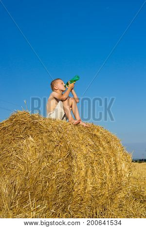 The boy sat on a bale of hay and drank water from a bottle