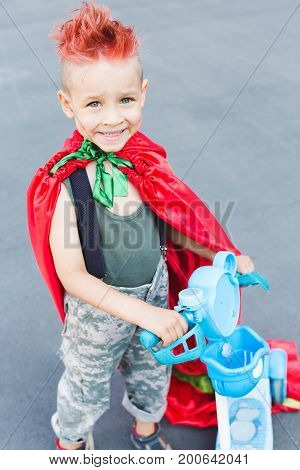 Happy little child playing superhero. Kid having fun outdoors. Kid superhero in a red cloak.A little boy with red hair. The boy is riding a scooter. Child in uniform