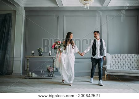 Cheerful Bride And Groom Holding Hands. Newlyweds Laughing And Looking At Each Other. Artwork. Weddi
