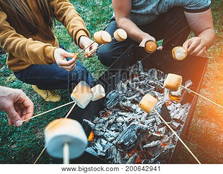 Friends by campfire making fried marshmallows. People fry marshmallows around the fire together.