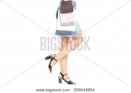 Legs in shoes young girl a lot of cardboard packages bags on white background isolation
