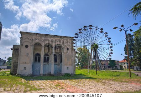 Abandoned House of Culture and old rusty abandoned Ferris wheel in the amusement park in Ochamchira, Abkhazia