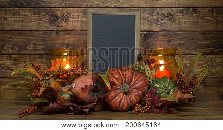 Autumn candle decoration on a rustic wood background with copy space