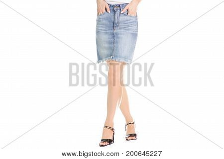 Legs in shoes young girl denim skirt on white background isolation