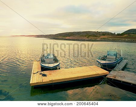 Fishing Boat At Sunset Calm Water. A Motorboat For Sport Fishing Tied To A Wooden Pier