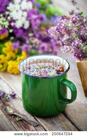 Enameled Mug Of Thyme Healing Herbs And Medicinal Herbs Bunch On Background. Herbal Medicine.