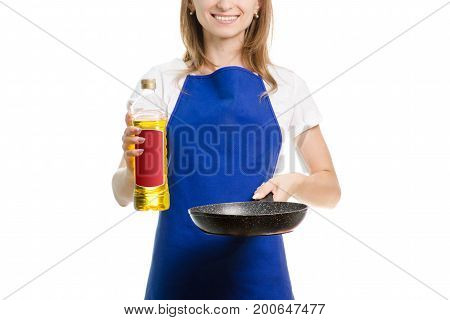 Young woman with a frying pan and oil in hands on a white background isolation