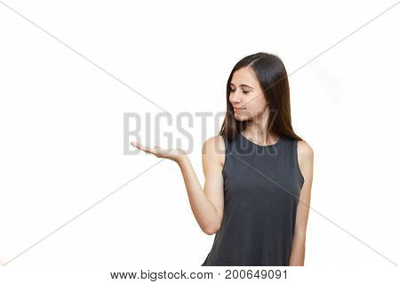 Young excited woman standing happy smiling holding her hand showing something on the open palm. Girl emotions. White background.